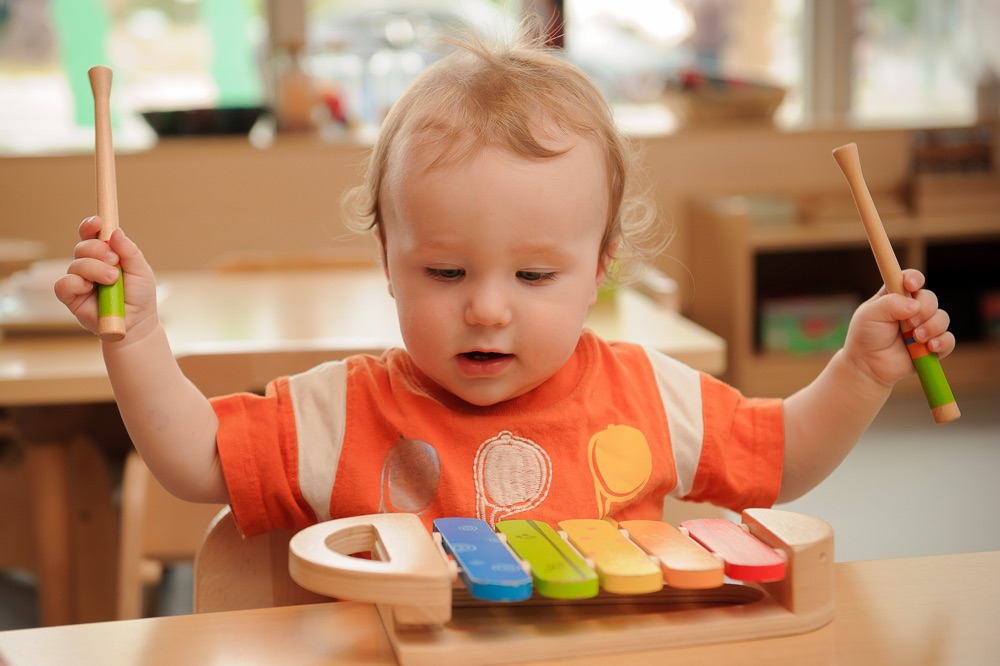 child under 2 playing a xylophone