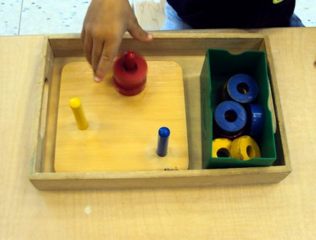 child working with 3 coloured dowels with small rings