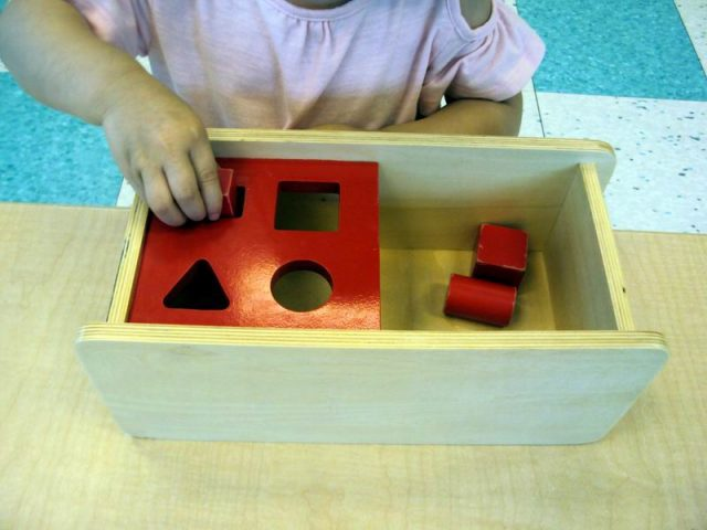 child inserting geometric solids into an imbucare box