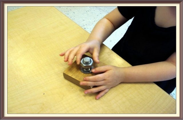 child working with a bolt, washer and nut