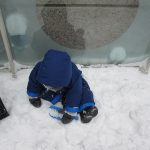 child under 2 scooping snow
