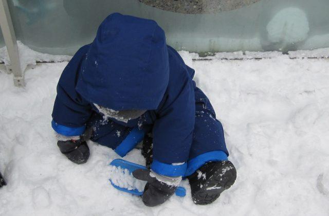 child under 2 scooping snow