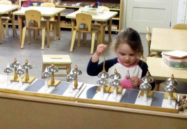 Child playing the Montessori bells