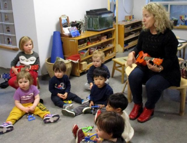 Adrianna playing the ukulele with children observing