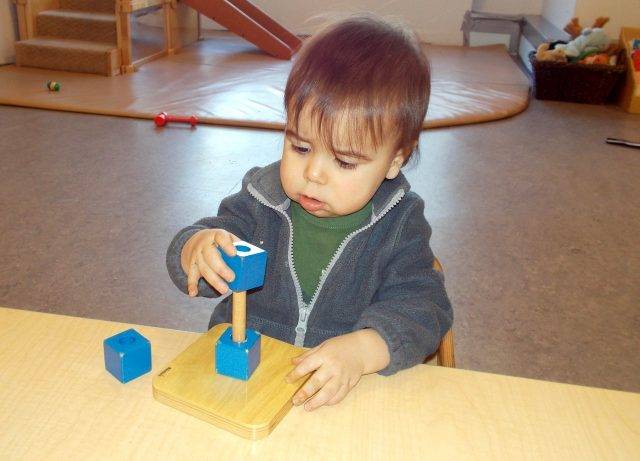 Child under 2 placing a cube on a dowel