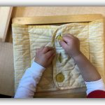 Child under 3 working on button dressing frame