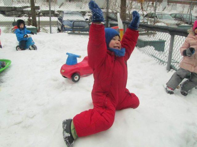Child smiling on a snow mound