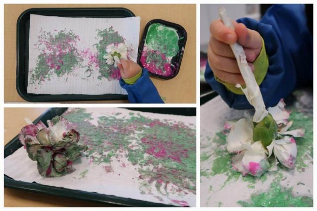 Child painting with a flower